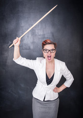 Angry screaming teacher with pointer on blackboard background