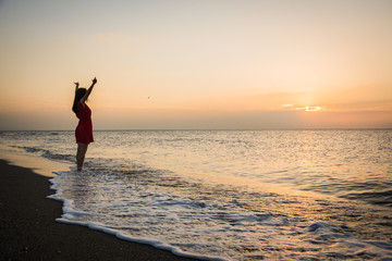 Girl in a red dress at sunrise on a golden beach watching the sea silhouette