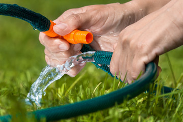 hands  connecting garden hoses for irrigation
