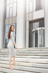 Business woman standing on the stairs in a half-turn looking away. Business concept.
