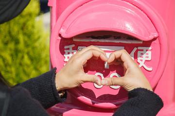 ピンクのポストの前でハートマークを指で作る