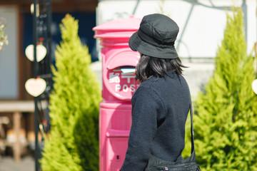 ピンクのポストに手紙を投函する女性