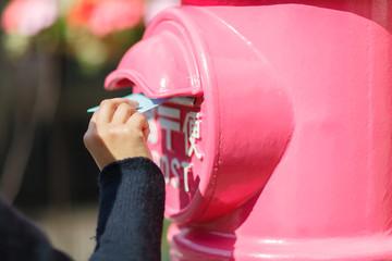 ピンクのポストに手紙を投函する