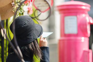 ピンクのポストに手紙を投函しようとする女性
