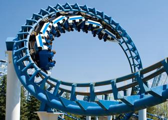 Cork-screw Rollercoaster and Ferris-Wheel at amusement park. Slight motion blur on Rollercoaster cars