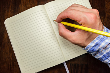 Man writing in a lined notebook with a yellow pencil.