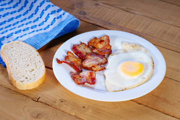 Fried egg with bacon, sliced bread and towel