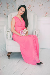 Brunette girl in pink dress sitting white armchair with bouquet of flowers in their hands