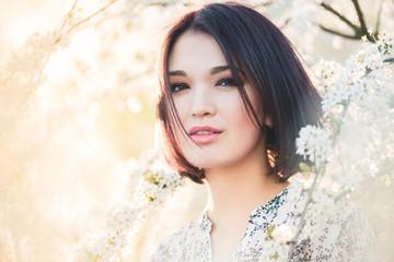 Beautiful Chinese girl among cherry sakura blossoms