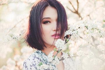 Beautiful young woman in blooming sakura