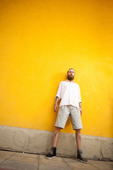 Cool looking bearded guy on yellow wall