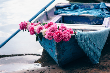 alone blue boat on the river, decorated with flowers