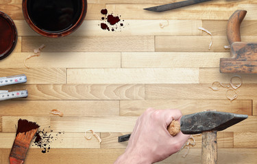 Woodworking tools with free space for text. Hammer and chisel in hand, beside is brush, paint, wood plane, ruler, shavings.