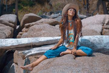 Happy summer girl sitting on the stone. Boho style