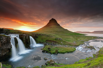 Wall Murals Waterfalls Amazing sunset the top of Kirkjufellsfoss waterfall with Kirkjufell mountain in the background on the north coast of Iceland's Snaefellsnes peninsula taken white a long shutter speed.