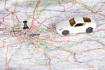White toy car and a black pin on a map. Shallow depth of field.
