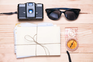 Vintage camera, sunglasses, bunch of letters and a compass on a