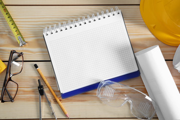 Notebook with construction tools on wooden background