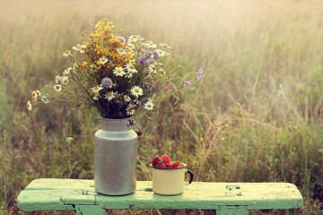 retro still life with flowers and berries in the rustic landscap/ bouquet wildflowers in a can on a wooden bench standing next to a cup of strawberries