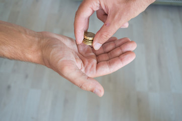 Man giving coins to another person