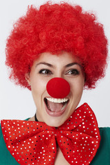 Happy clown in red wig and bow tie