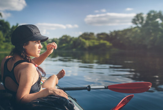 Summer vacation - Back view of young woman kayaking on river.