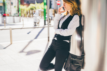 young beautiful caucasian millennial blonde hair businesswoman talking smart phone outdoor in the city, overlooking - communication, work, business concept