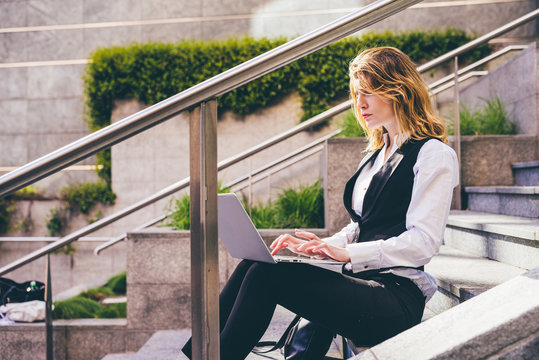 Young handsome caucasian blonde hair millennial businesswoman sitting on a staircase using computer, tapping keyboard - technology, work, business concept