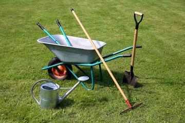 Wheelbarrow and gardening tools on green grass