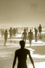 Defocus silhouettes of beachgoers fill the shore of Ipanema at sunset on a summer afternoon in Rio de Janeiro, Brazil