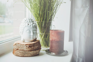 White buddha head figurine on wooden stand with big brown candle  a  windowsill, green floral plant background. Home object decor in interior. Place for text, free copy space.