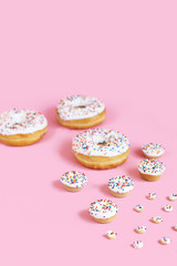 Donuts in various sizes against pink background