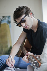 Young musician writing songs on an acoustic guitar