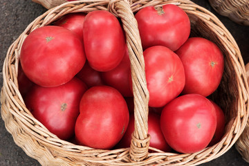 Big tomatoes in wooden basket. Top view, High resolution product.
