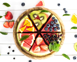 Sliced juicy watermelon pizza on white wooden table.  Watermelon, blueberries, grapefruit, orange,kiwi,strawberry,black currant,mint.Concept for healthy Eating. Eye bird view.