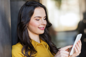 smiling young woman or girl texting on smartphone