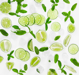 Fototapete - Limes, fresh mint and ice for mojito on white background.