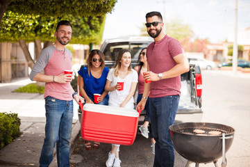 Friends bringing drinks to a barbecue