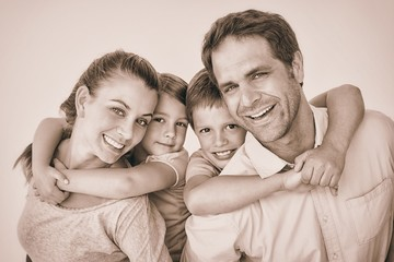 Smiling young family looking at camera together