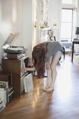 Young woman choosing a record album from a shelf