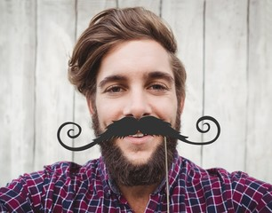 Composite image of happy hipster against wooden fence