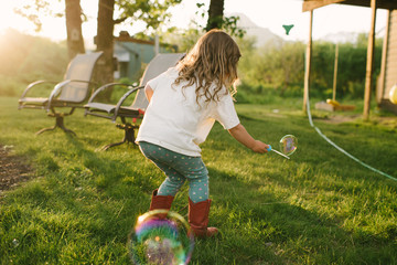 Young girl playing with bubbles in garden