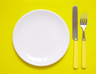An empty dinner plate with knife and fork arranged as a place setting on a yellow background