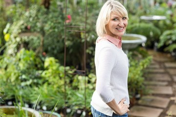 Happy mature woman with hand on hip at greenhouse