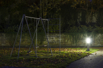 Ein leerer Spielplatz mit Kinderschaukeln nachts mit Nebel und gruseliger Atmosphäre