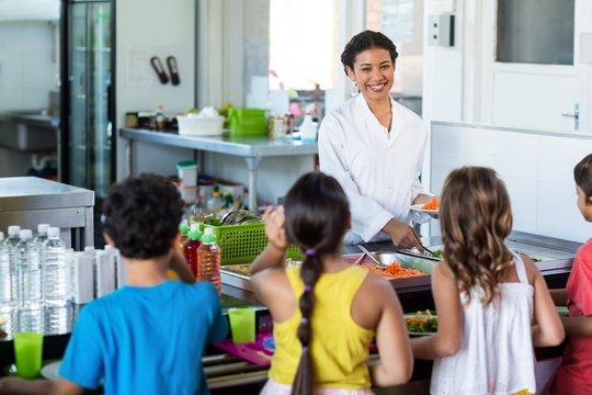 Woman serving food to schoolchildren