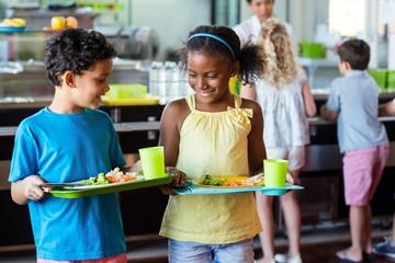 Schoolchildren holding food tray in canteen