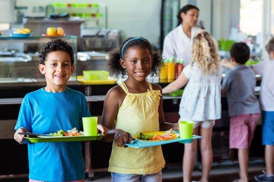Happy schoolchildren holding food tray in canteen