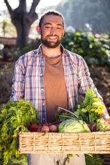 Happy hipster gardener holding fresh vegetables at garden