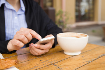 Woman with smartphone sitting in an outdoor cafe and drinking coffee. Breakfast before working day. Cappuccino and croissant on a wooden table. Girl in the cafe.